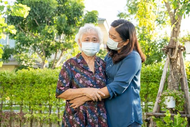 Asiatische ältere frau mit pflegekraft, die mit glücklichem im naturpark geht.