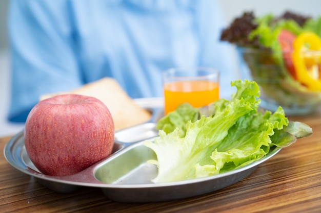 Asiatische ältere frau patient, die frühstück gemüse gesundes essen isst