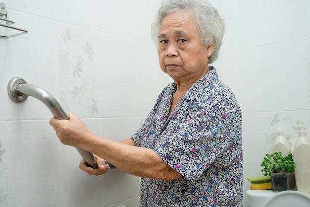 Asiatische ältere frau patient verwenden toilette badezimmergriff sicherheit.