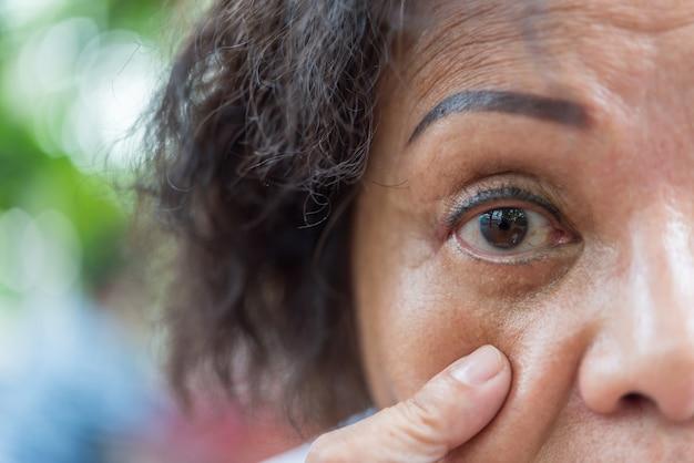 Asiatische ältere frauen zeigen ihre augen und augenbrauentätowierung