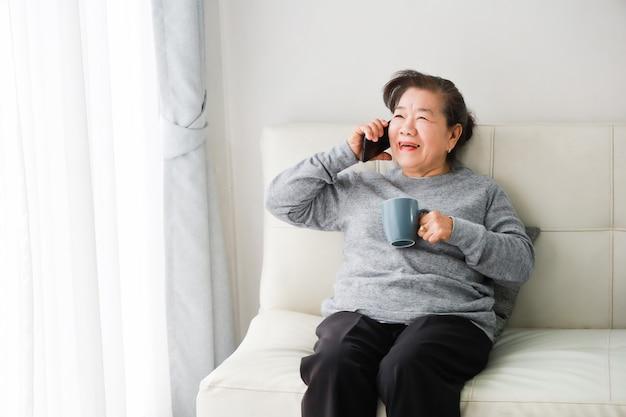 Asiatische ältere frauenmutter, die mit handy spricht und kaffee im wohnzimmer trinkt