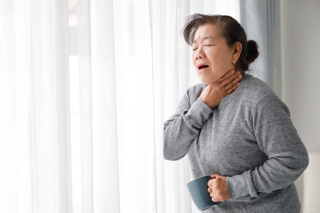 Asiatische ältere frauenmutter und sohn des jungen mannes im blauen hemd massieren seine mutter im wohnzimmer