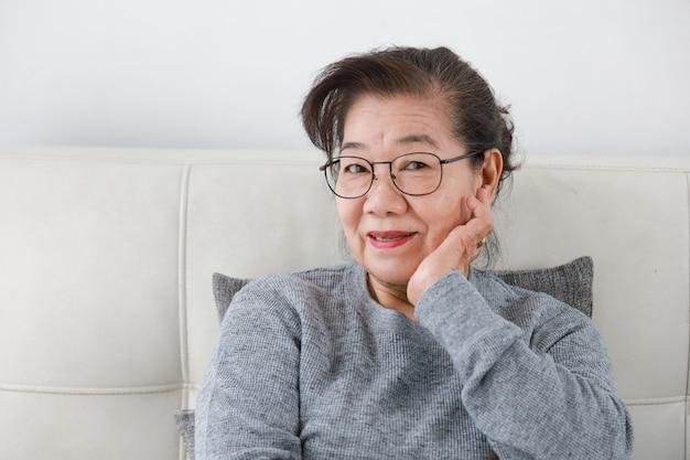 Asiatische ältere großmutter im glücklichen gesicht des wohnzimmerlebensstils