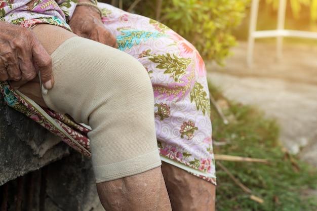 Asiatische ältere leute oder ältere frau, die die kniestütze tragen