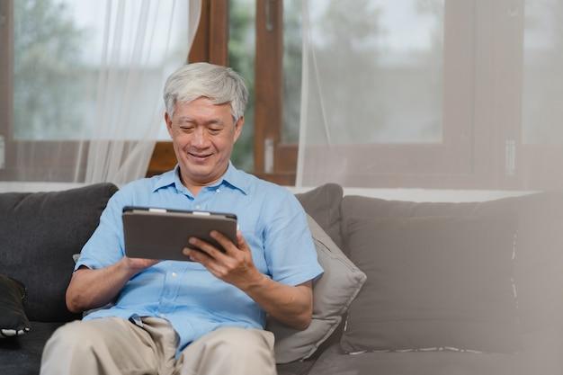 Asiatische ältere männer, die zu hause tablette verwenden. asiatische ältere chinesische männliche suchinformationen über wie zur guten gesundheit auf internet beim auf sofa im konzept des wohnzimmers zu hause liegen.