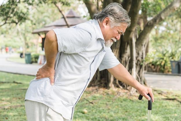 Asiatische ältere menschen, die rückenschmerzen haben.