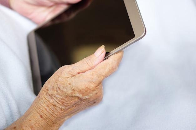 Asiatische ältere oder ältere alte dame frau benutzt oder spielt tablette auf einem blauen tuch. gesundheits-, medizin- und technologiekonzept.