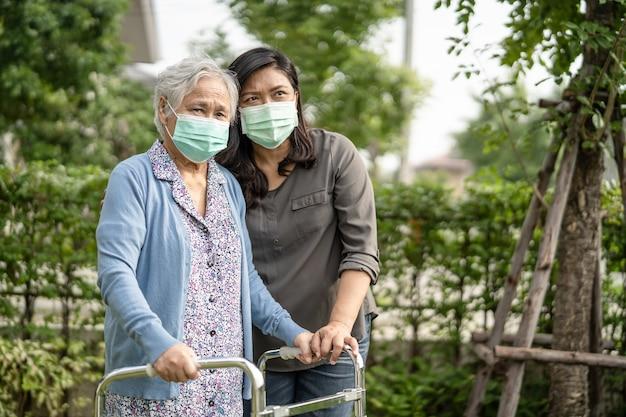 Asiatische ältere oder ältere alte dame frau, die eine gesichtsmaske neue normalität im park zum schutz der sicherheitsinfektion covid-19 coronavirus trägt.