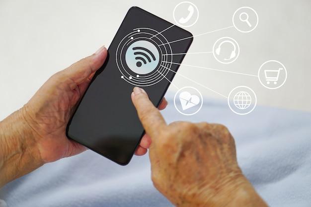 Asiatische ältere oder ältere alte dame frau, die smartphone hält