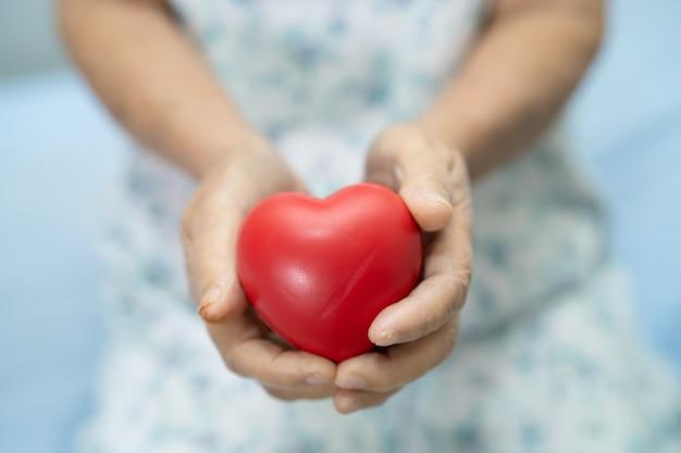 Asiatische ältere oder ältere alte dame patientin, die rotes herz in der hand auf dem bett in der krankenstation hält, gesundes, starkes medizinisches konzept