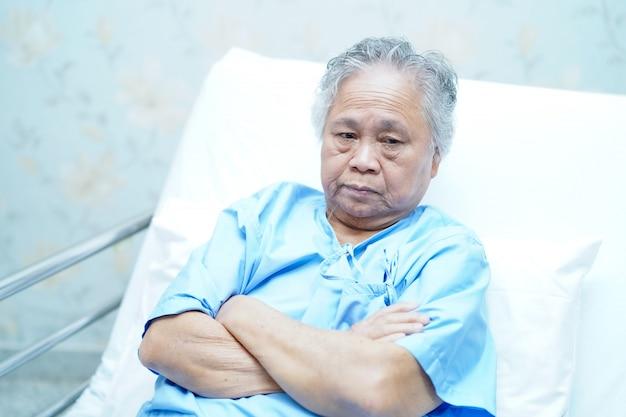 Asiatische ältere oder ältere alte frau patientin lächeln helles gesicht beim sitzen auf dem bett in der krankenstation: gesundes starkes medizinisches konzept