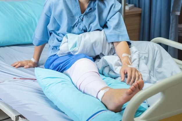 Asiatische ältere oder ältere alte patientin, die mit bandagekompressions-knieortheseunterstützungsverletzung auf dem bett im krankenpflegestationskrankenhaus liegt.