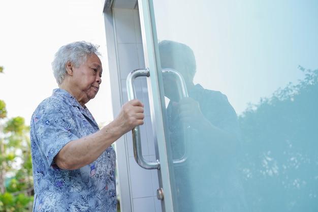 Asiatische ältere oder ältere geduldige gebrauchstoilettenbadezimmergriff-sicherheitsschiebetür alter dame