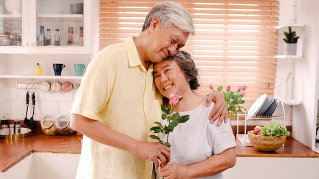 Asiatische ältere paare, die dem glücklichen lächeln und halten der blume und schauen zur kamera sich fühlen, während zu hause in der küche sich entspannt. lebensstil-ältere familie genießen konzept der zeit zu hause.