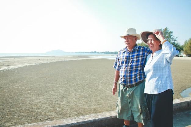 Asiatische ältere paare, die durch das meer sich umarmen glücklich nach ruhestand