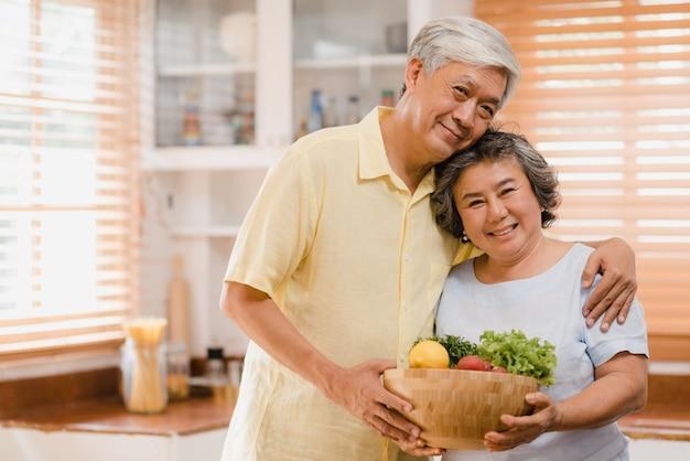 Asiatische ältere paare, die glücklichem lächeln und frucht halten und zur kamera schauen schauen, während sie sich in der küche zu hause entspannen.