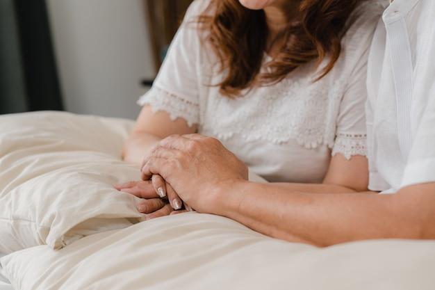 Asiatische ältere paare, die ihre hände beim schlafzimmer zusammennehmen, paargefühl glücklich teilen und das lügen auf bett zu hause stützen. älteres konzept der familie des lebensstils zu hause.