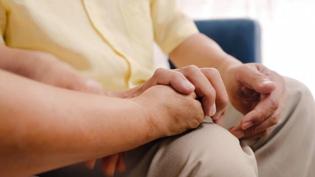Asiatische ältere paare, die ihre hände beim zusammennehmen im wohnzimmer, glücklichen anteil der paare und unterstützung sich liegend auf sofa zu hause liegen halten.