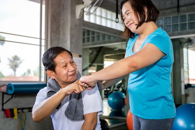 Asiatische ältere paare, die in der sportkleidung trainiert an der turnhalle lächeln.
