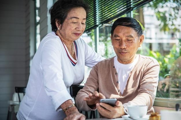 Asiatische ältere paare, die smartphone während teatime betrachten