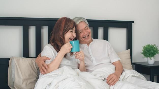 Asiatische ältere paare, die zu hause auf bett sprechen. asiatische ältere chinesische großeltern, ehemann und frau, die glücklich sind, trinken kaffee, nachdem sie beim auf bett im konzept des schlafzimmers zu hause morgens liegen aufgewacht sind.