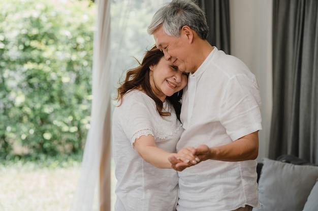 Asiatische ältere paare, die zusammen tanzen, während musik im wohnzimmer zu hause hören, süßes paar genießen liebesmoment beim haben des spaßes, wenn sie zu hause entspannt werden. ältere familie des lebensstils entspannen sich zu hause konzept.