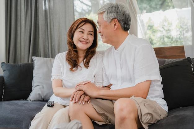 Asiatische ältere paare entspannen sich zu hause. asiatische ältere chinesische großeltern, glückliche lächelnumarmung des ehemanns und der frau, die zusammen beim auf sofa im konzept des wohnzimmers zu hause liegen spricht.