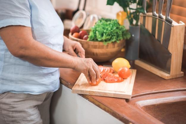 Asiatische ältere paare schneiden tomaten bereiten bestandteil für die herstellung des lebensmittels in der küche zu