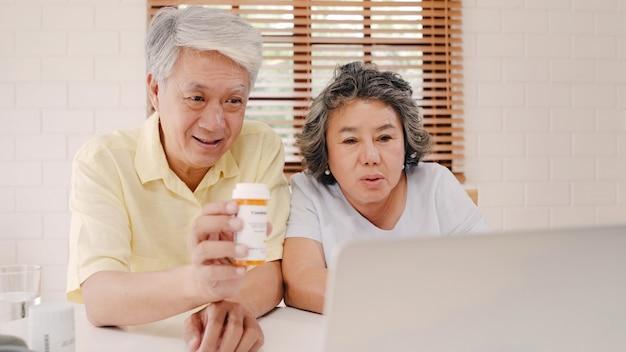 Asiatische ältere paare unter verwendung der laptopkonferenz mit doktor über medizininformationen im wohnzimmer, paare unter verwendung der zeit zusammen beim auf sofa zu hause liegen.