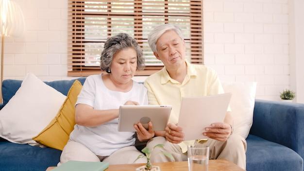 Asiatische ältere paare unter verwendung der tablette, die zu hause im wohnzimmer fernsieht, paare genießen liebesmoment beim auf sofa liegen, wenn sie zu hause entspannt werden.