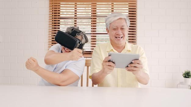 Asiatische ältere paare unter verwendung der tablette und des simulators der virtuellen realität, die spiele im wohnzimmer spielen, paare, die unter verwendung der zeit glücklich sich fühlen, die zusammen auf tabelle zu hause liegt.