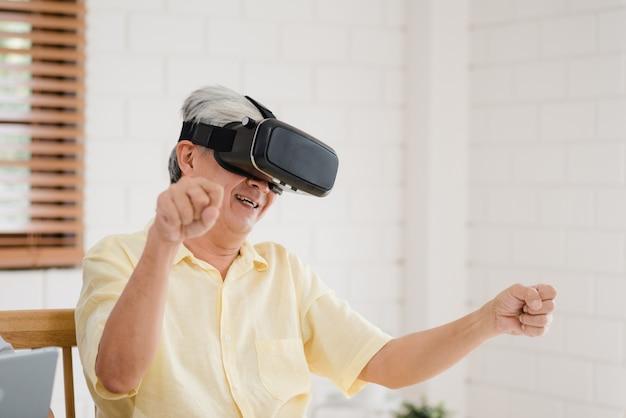 Asiatische ältere paare unter verwendung der tablette und des simulators der virtuellen realität, die spiele im wohnzimmer spielen