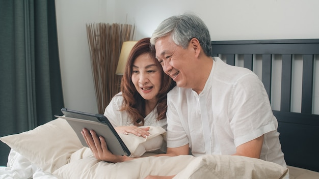 Asiatische ältere paare unter verwendung der tablette zu hause. asiatische ältere chinesische großeltern, videoanruf, der mit familienenkelkind spricht, scherzt beim auf bett im konzept des schlafzimmers zu hause morgens liegen.