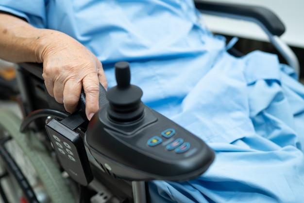 Asiatische ältere patientin auf elektrischem rollstuhl mit fernbedienung im krankenhaus.