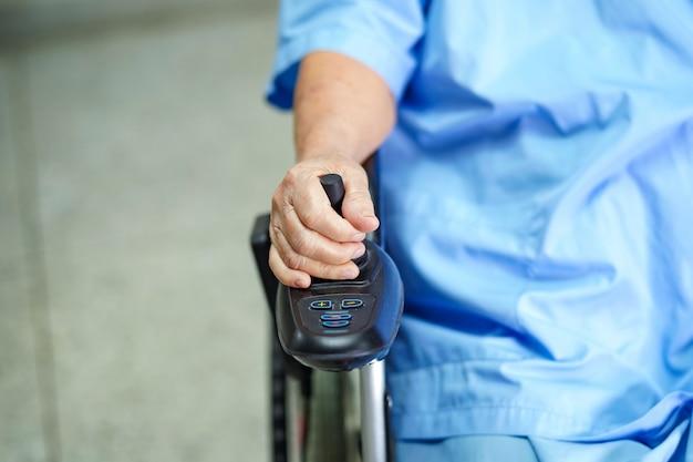 Asiatische ältere patientin auf elektrischem rollstuhl mit fernbedienung.