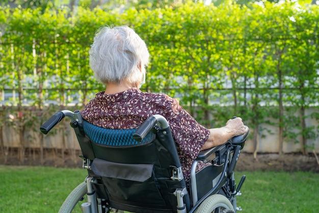 Asiatische ältere patientin auf elektronischem rollstuhl im park.