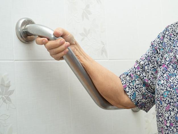 Asiatische ältere patientin benutzt toiletten-badezimmer-griff-sicherheit im krankenhaus