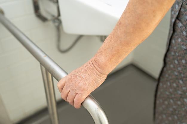 Asiatische ältere patientin benutzt toilettenbadezimmer-griffsicherheit im pflegekrankenhaus