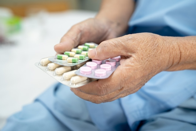 Asiatische ältere patientin, die antibiotika-kapselpillen in blisterverpackung hält