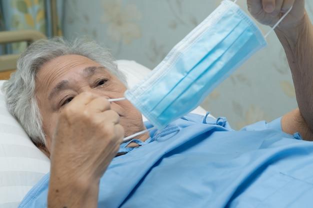 Asiatische ältere patientin, die eine gesichtsmaske im krankenhaus trägt, um covid-19-virus zu schützen.