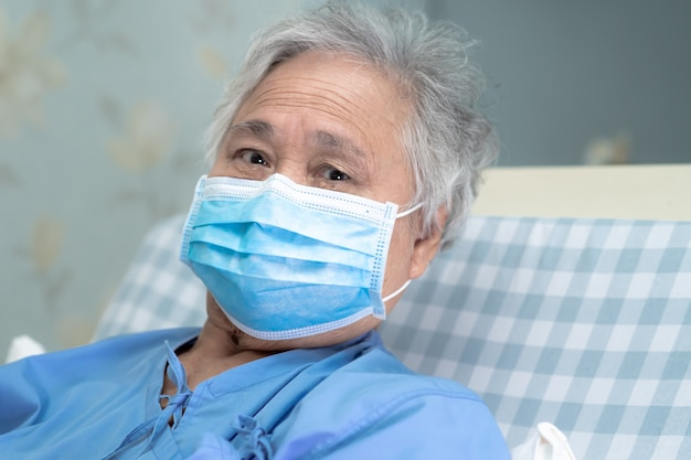 Asiatische ältere patientin, die eine gesichtsmaske trägt, um coronavirus oder covid-19-virus zu schützen.