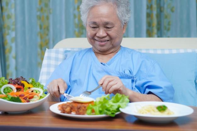 Asiatische ältere patientin, die frühstück im krankenhaus isst.