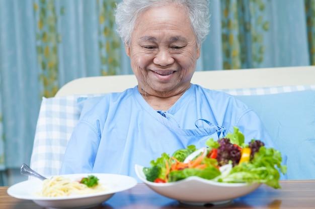 Asiatische ältere patientin, die frühstück isst.
