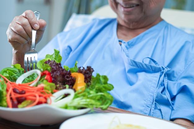 Asiatische ältere patientin, die frühstücksgemüse im krankenhaus isst.