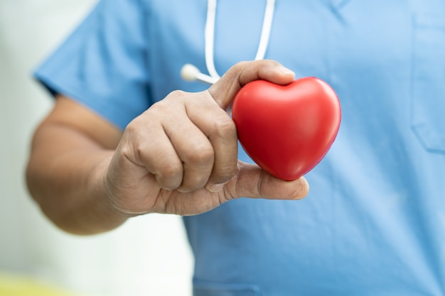 Asiatische ältere patientin, die im krankenhaus rotes herz in der hand hält