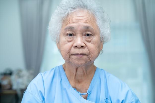 Asiatische ältere patientin, die im pflegekrankenhaus sitzt