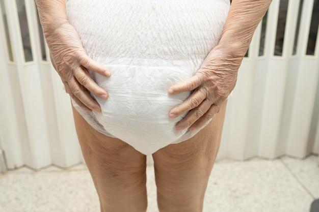 Asiatische ältere patientin, die inkontinenzwindel im krankenhaus trägt.