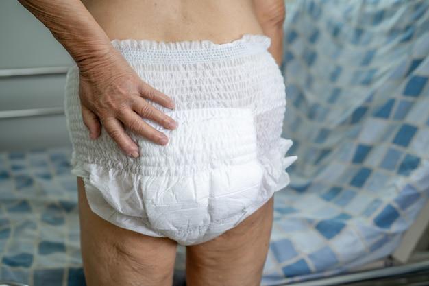 Asiatische ältere patientin, die inkontinenzwindel im pflegekrankenhaus trägt