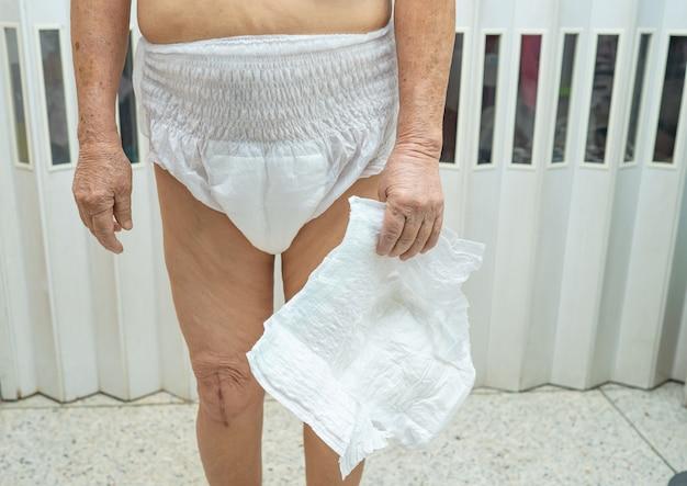 Asiatische ältere patientin, die inkontinenzwindel trägt.