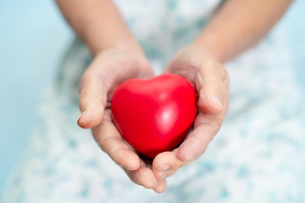 Asiatische ältere patientin, die rotes herz in ihrer hand hält